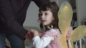 Ειλικρινές παιδί της Νίκαιας που ντύνει επάνω από τον μπαμπά της όπως μια ρόδινη νεράιδα σε αργή κίνηση SF απόθεμα βίντεο