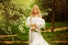 Ειλικρινής πηδώντας ξένοιαστη λατρευτή γυναίκα στο πεδίο με τα λουλούδια στο θερινό ηλιοβασίλεμα στοκ εικόνες
