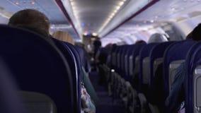 Ειλικρινής πυροβολισμός μεταξύ των καθισμάτων των επιβατών που κάθονται μέσα στο αεροπλάνο διακινούμενος απόθεμα βίντεο