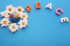 ΕΙΡΗΝΗ λέξης που γίνεται από τις επιστολές κοντά σε λίγο αριθμό μιας σφαίρας που περιβάλλεται από τα λουλούδια των άσπρων χρυσάνθ στοκ φωτογραφία