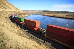 Ειρηνικά ταξίδια φορτηγών τρένων ένωσης κατά μήκος του ποταμού φιδιών στοκ εικόνα