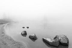 Ειρηνικός βράχος, βράχος στη λίμνη με την ομίχλη πέρα από τη λίμνη σε γραπτό Στοκ εικόνες με δικαίωμα ελεύθερης χρήσης