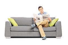 Ειρηνικός νεαρός άνδρας που διαβάζει τις ειδήσεις που κάθονται στον καναπέ Στοκ Εικόνες