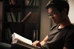 Ειρηνικό βιβλίο συνεδρίασης και ανάγνωσης νεαρών άνδρων στο σπίτι Στοκ Φωτογραφία