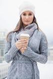 Ειρηνικό όμορφο brunette με τα χειμερινά ενδύματα στον καφέ εκμετάλλευσης Στοκ Φωτογραφίες