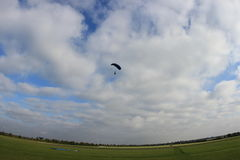 Εισερχόμενο skydiver, νεφελώδεις ουρανοί πέρα από τους σαφείς τομείς μια όμορφη ημέρα Στοκ φωτογραφία με δικαίωμα ελεύθερης χρήσης