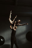 Ειδικευμένοι νέοι gymnasts που χορεύουν μαζί στο μαύρο χρωματισμένο στούντιο στοκ εικόνες με δικαίωμα ελεύθερης χρήσης
