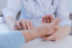 Ειδικευμένος επαγγελματίας που παίρνει τον υπομονετικό σφυγμό στο νοσοκομείο Στοκ Φωτογραφία