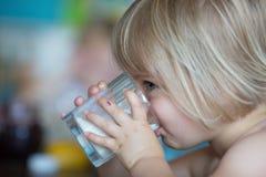 Ειλικρινές κοριτσάκι που έχει το πόσιμο γάλα προγευμάτων στο σπίτι στη θερινή ημέρα Στοκ φωτογραφία με δικαίωμα ελεύθερης χρήσης