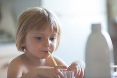Ειλικρινές κοριτσάκι που έχει το πόσιμο γάλα προγευμάτων στο σπίτι στη θερινή ημέρα Στοκ Φωτογραφία