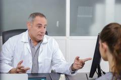 Ειλικρινής αρσενικός γιατρός που εξηγεί κάτι στο θηλυκό ασθενή Στοκ Εικόνες