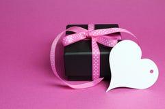 Ειδικό μικρό παρόν δώρο μαύρων κουτιών με τη ρόδινη κορδέλλα σημείων Πόλκα και την άσπρη ετικέττα δώρων μορφής καρδιών