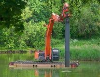 Ειδικό σκάφος, λειτουργώντας πλατφόρμα σε λειτουργία σε μια μικρή λίμνη Σημειωμένος spiles στο κατώτατο σημείο της λίμνης στοκ εικόνα με δικαίωμα ελεύθερης χρήσης