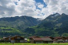 Ειδυλλιακό τοπίο στις Άλπεις στην άνοιξη με το παραδοσιακό σαλέ βουνών και τα φρέσκα πράσινα λιβάδια βουνών με τα λουλούδια Στοκ Φωτογραφία