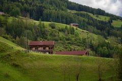 Ειδυλλιακό τοπίο στις Άλπεις στην άνοιξη με το παραδοσιακό σαλέ βουνών και τα φρέσκα πράσινα λιβάδια βουνών με τα λουλούδια Στοκ εικόνες με δικαίωμα ελεύθερης χρήσης