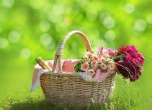 Ειδύλλιο, αγάπη, έννοια ημέρας βαλεντίνων ` s - ψάθινο καλάθι με την ανθοδέσμη των λουλουδιών, κρασί μπουκαλιών στη χλόη Φρέσκος  Στοκ Φωτογραφίες