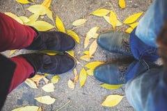 Ειδύλλιο φθινοπώρου Πόδια του άνδρα και της γυναίκας στα πεσμένα φύλλα Στοκ Φωτογραφίες