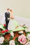 Ειδώλια της νύφης και του νεόνυμφου σε ένα γαμήλιο κέικ Στοκ Εικόνες