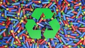 Εκατοντάδες των ζωηρόχρωμων μπαταριών και στη μέση το πράσινο ανακύκλωσης σύμβολο στοκ φωτογραφία