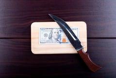 Εκατό δολάρια σε έναν τέμνοντα πίνακα με ένα μαχαίρι, τοπ άποψη Στοκ εικόνα με δικαίωμα ελεύθερης χρήσης