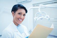 Εκθέσεις ανάγνωσης οδοντιάτρων χαμόγελου θηλυκές στοκ εικόνα με δικαίωμα ελεύθερης χρήσης