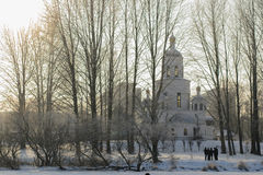Εκκλησία στο χειμερινό πάρκο από την παγωμένη λίμνη με τις σκιαγραφίες των ανθρώπων Στοκ εικόνα με δικαίωμα ελεύθερης χρήσης