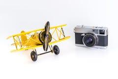 Εκλεκτής ποιότητας αεροπλάνο παιχνιδιών με την εκλεκτής ποιότητας κάμερα ταξιδιού που απομονώνεται στην άσπρη έννοια ταξιδιού στοκ φωτογραφία με δικαίωμα ελεύθερης χρήσης