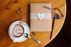Εκλεκτής ποιότητας ημερολόγιο με τη χειροποίητη κάλυψη, υφαντική καρδιά Φλυτζάνι του καφέ latte ή cappuccino στον ξύλινο πίνακα στοκ εικόνα