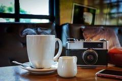 Εκλεκτής ποιότητας κάμερα με το φλυτζάνι, τα γυαλιά και το smartphone καφέ στο TA στοκ φωτογραφία