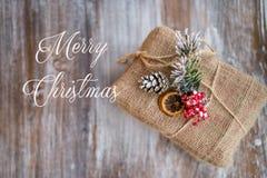 Εκλεκτής ποιότητας κάρτα Χριστουγέννων Η Χαρούμενα Χριστούγεννα επιγραφής Δώρο Χριστουγέννων στο εκλεκτής ποιότητας ξύλινο υπόβαθ Στοκ Εικόνες