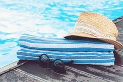 Εκλεκτής ποιότητας καπέλο παραλιών θερινού ψάθινο αχύρου, γυαλιά ήλιων, μπλε πισίνα πετσετών πλησίον, τροπικό υπόβαθρο στοκ εικόνες με δικαίωμα ελεύθερης χρήσης