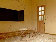 Εκλεκτής ποιότητας καρέκλα και πίνακας σε μια αποσυντεθειμένη παλαιά τάξη Στοκ Εικόνες