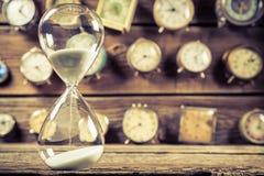 Εκλεκτής ποιότητας κλεψύδρα στο υπόβαθρο φιαγμένο από ρολόγια Στοκ εικόνες με δικαίωμα ελεύθερης χρήσης