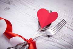 Εκλεκτής ποιότητας κουτάλι και δίκρανο με ένα κώλυμα και καρδιά για την ημέρα βαλεντίνων ` s σε έναν ξύλινο Στοκ φωτογραφία με δικαίωμα ελεύθερης χρήσης