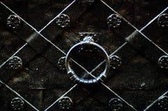Εκλεκτής ποιότητας λαβή πορτών σε μια μαύρη πόρτα σιδήρου με τα σφυρηλατημένα προϊόντα, έννοια του αυθεντικού objectsn στοκ εικόνες
