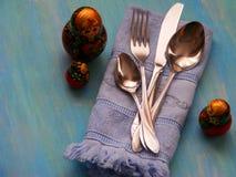 Εκλεκτής ποιότητας μαχαίρι, κουτάλι και δίκρανο με το ρωσικό matrioshka κουκλών στο μπλε ξύλινο υπόβαθρο Στοκ Φωτογραφία