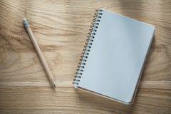 Εκλεκτής ποιότητας μολύβι σημειωματάριων στον ξύλινο πίνακα Στοκ Φωτογραφίες