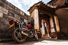 Εκλεκτής ποιότητας μοτοσικλέτα μπροστά από το σπίτι παραδοσιακού κινέζικου στοκ εικόνα