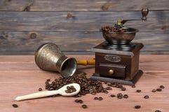 Εκλεκτής ποιότητας μύλος καφέ, δοχείο καφέ χαλκού Τούρκου και φασόλια καφέ στο καφετί ξύλινο υπόβαθρο Στοκ Φωτογραφία