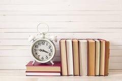 Εκλεκτής ποιότητας ξυπνητήρι και σωρός των βιβλίων στον ξύλινο πίνακα Έννοια ο στοκ εικόνες με δικαίωμα ελεύθερης χρήσης