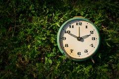 Εκλεκτής ποιότητας ξυπνητήρι σε ένα υπόβαθρο της πράσινης χλόης διάστημα αντιγράφων στοκ φωτογραφία