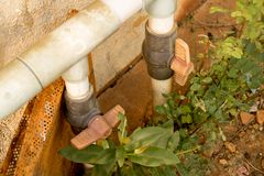 Εκλεκτής ποιότητας παλαιά πλαστική στρόφιγγα νερού με τη βαλβίδα PVC - εγκαταλειμμένος κήπος με τις πράσινες εγκαταστάσεις στοκ εικόνες με δικαίωμα ελεύθερης χρήσης