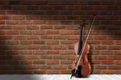 Εκλεκτής ποιότητας παλαιό βιολί κοντά στο υπόβαθρο τουβλότοιχος στοκ εικόνες με δικαίωμα ελεύθερης χρήσης