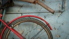 Εκλεκτής ποιότητας παλαιό κόκκινο ποδήλατο στον τραχύ χρωματισμένο μπλε τοίχο με το αγροτικό ξύλο στοκ φωτογραφία