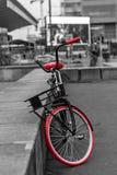 Εκλεκτής ποιότητας ποδήλατο με τις πορτοκαλιές ρόδες ενάντια στο σκηνικό της πόλης στοκ εικόνες