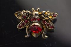 Εκλεκτής ποιότητας πόρπη υπό μορφή μελισσών φιαγμένων από χάντρες, ύφασμα και κρύσταλλα, που ψαλιδίζουν σε ένα παλαιό μαύρο υπόβα Στοκ Φωτογραφίες