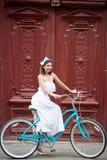 Εκλεκτής ποιότητας πόρτα στην παλαιά πόλη στο κορίτσι πρώτου πλάνου στο ποδήλατο στοκ εικόνες