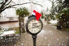 Εκλεκτής ποιότητας ρολόι οδών με τη Χαρούμενα Χριστούγεννα κειμένων και καπέλο Άγιου Βασίλη σε τους κατά τη διάρκεια των χιονοπτώ Στοκ φωτογραφία με δικαίωμα ελεύθερης χρήσης