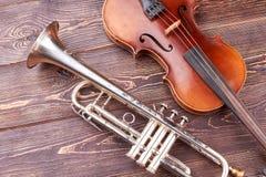 Εκλεκτής ποιότητας σάλπιγγα και βιολοντσέλο στο ξύλινο υπόβαθρο στοκ εικόνες