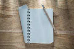 Εκλεκτής ποιότητας σπειροειδές κενό μολύβι σημειωματάριων στον ξύλινο πίνακα Στοκ Εικόνα
